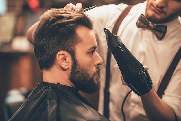 Stai già bene. vista laterale ravvicinata di un giovane uomo barbuto che viene curato dal parrucchiere