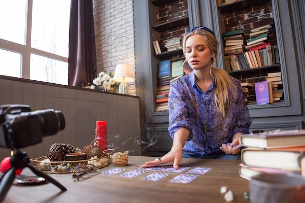 Guardando al futuro. giovane donna intelligente che ha una sessione di predizione della fortuna durante la registrazione in video