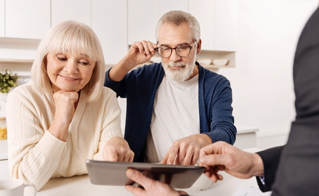Guardando il nostro futuro progetto di casa. agente immobiliare istruito capace intelligente che lavora con una coppia di clienti in pensione mentre mostra il progetto della casa e utilizza il dispositivo