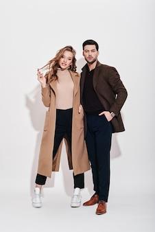 Guardando perfetto insieme coppia attraente e ben vestita in posa in studio isolato su gray