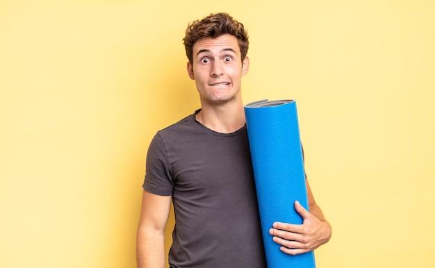 Guardando perplesso e confuso, mordendosi il labbro con un gesto nervoso, non conoscendo la risposta al problema. concetto di tappetino da yoga