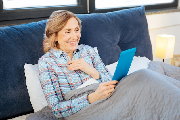 Guardando sullo schermo. tranquilla signora adulta che riposa a letto durante la routine mattutina e porta una compressa blu in entrambe le mani