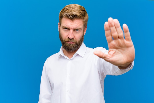 Guardando serio, severo, dispiaciuto e arrabbiato mostrando il palmo aperto facendo gesto di arresto