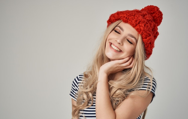 Alla ricerca di bionde sexy in cappello rosso lavorato a maglia e t-shirt a righe ritagliata vista primo piano.