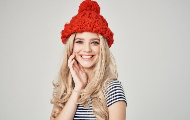 Alla ricerca di bionde sexy in cappello rosso lavorato a maglia e t-shirt a righe ritagliata vista primo piano
