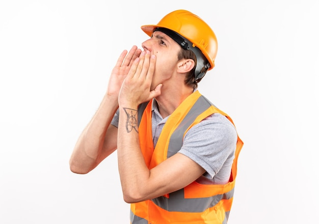 Guardando lato giovane costruttore in uniforme che chiama qualcuno isolato sul muro bianco