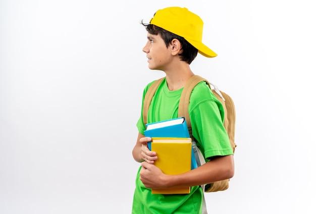 Guardando lato giovane scuola ragazzo che indossa uno zaino con cappuccio che tiene libri isolati sul muro bianco con spazio copia
