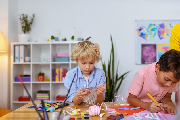 Guardando gli adesivi. scolaro dai capelli biondi che guarda gli adesivi mentre fa le decorazioni a lezione