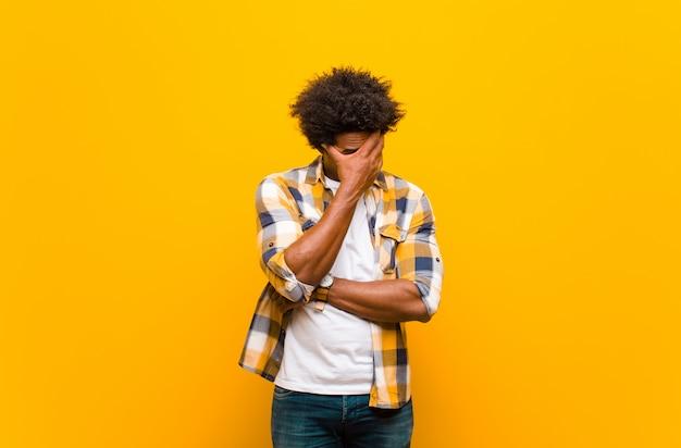 Sembra stressato, vergogna o turbato, con mal di testa, coprendosi il viso con la mano
