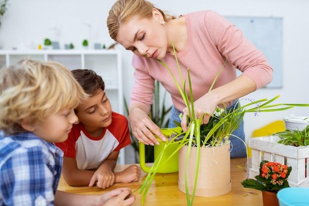 Guardando insegnante. due ragazzi carini che guardano l'insegnante si sentono attenti mentre tagliano i bordi asciutti della pianta