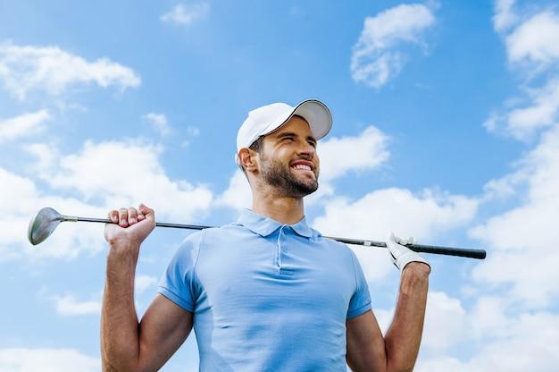 Guardando verso il successo. inquadratura dal basso di un giovane giocatore di golf felice che tiene in mano il conducente e sorride con il cielo blu come sfondo