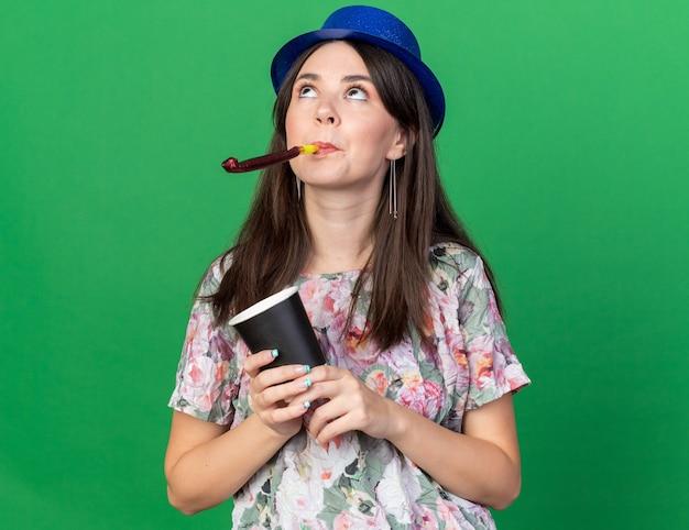 Cercando la giovane bella ragazza che indossa il cappello da festa che soffia il fischio della festa tenendo una tazza di caffè