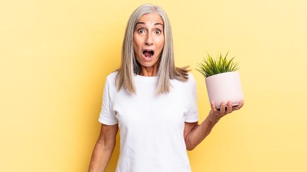 Sembrando molto scioccato o sorpreso, fissando con la bocca aperta dicendo wow con in mano una pianta decorativa