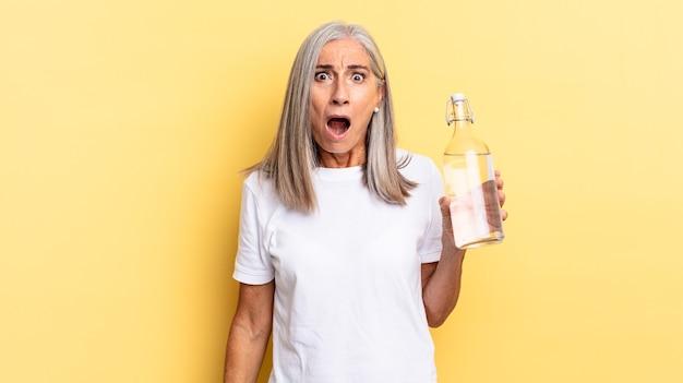Sembrando molto scioccato o sorpreso, fissando con la bocca aperta dicendo wow e tenendo in mano una bottiglia d'acqua