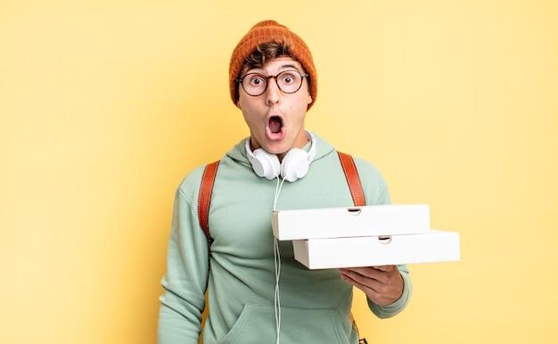 Sembrando molto scioccato o sorpreso, fissando con la bocca aperta dicendo wow. concetto di pizza