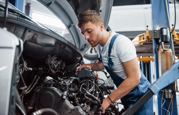 Guarda dentro la trasmissione. l'impiegato con l'uniforme di colore blu lavora nel salone dell'automobile.