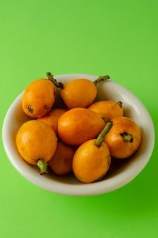 Frutti del nespolo in una ciotola bianca su verde intenso