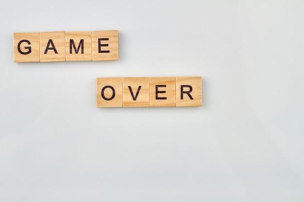 Perdi il concetto di gioco. game over realizzato con blocchi di legno isolati su sfondo bianco.