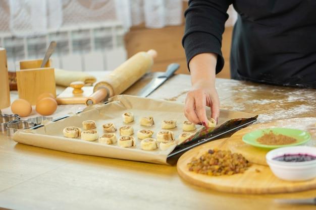 à â¡lose up femmina baker mano mette panini alla cannella con spezie e cacao sulla teglia con carta pergamena