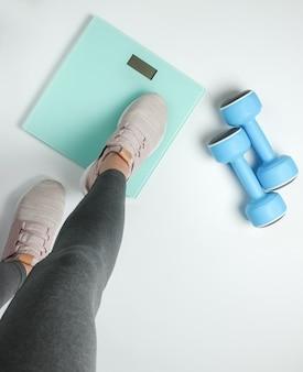Perdere peso, dieta, concetto di fitness. la donna sportiva che indossa leggings e scarpe da ginnastica misura il suo peso con bilance da pavimento su uno sfondo bianco. vista dall'alto