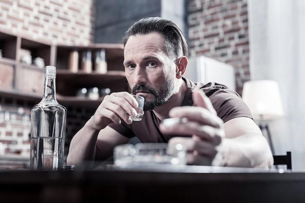 In perdita. uomo triste triste e triste che mette la mano sul tavolo e beve vodka senza sapere cosa fare per risolvere il suo problema