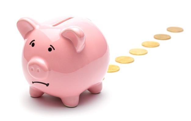Perdita di denaro salvadanaio rosa che perde monete d'oro isolate su uno sfondo bianco cattivo investimento