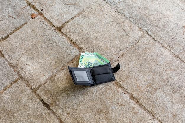 Portafoglio in pelle nera persa con denaro in euro su strada