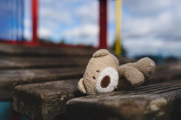 Orsacchiotto smarrito sdraiato sul ponte di legno al parco giochi in una giornata uggiosa, bambola orso bruno faccia solitaria e triste sdraiata da sola nel parco, giocattolo perso o concetto di solitudine, giornata internazionale dei bambini scomparsi