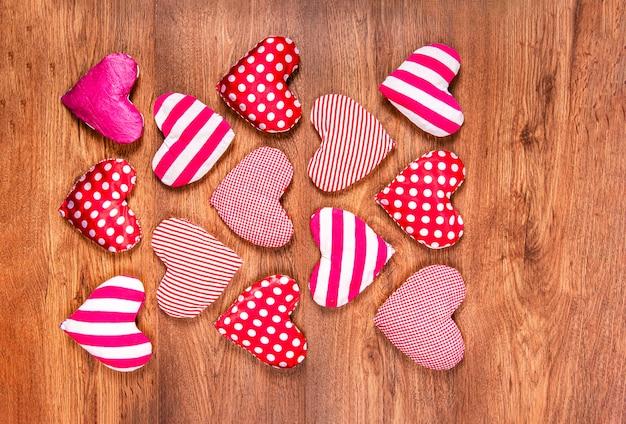 Un sacco di cuori rossi luminosi fatti a mano fatti di tessuto a pois o gabbia e striscia su uno sfondo di legno per la decorazione per le vacanze