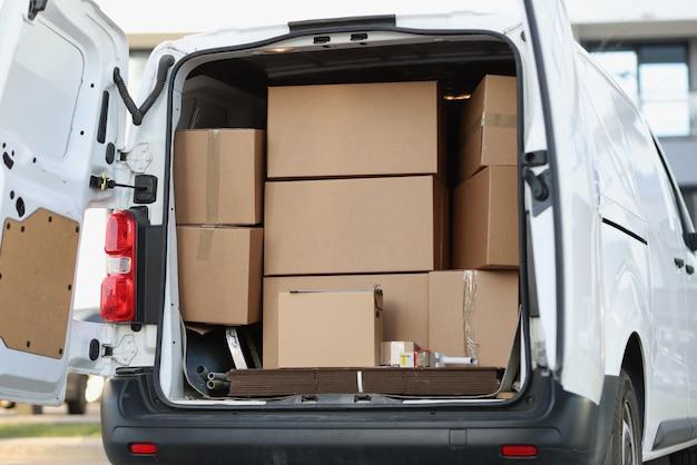 Molte scatole di cartone sono in minivan con il primo piano della porta aperta
