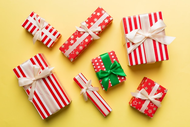 Molte scatole regalo di natale in carta colorata decorata sul tavolo, vista dall'alto da vicino. molti presentano il regalo di capodanno.