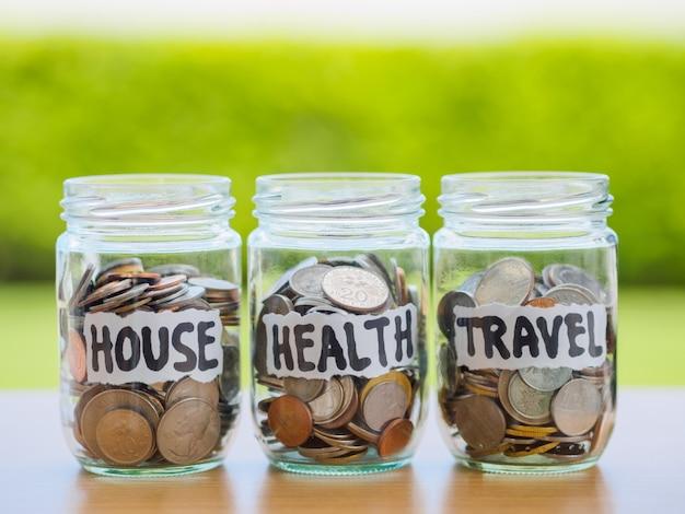 Un sacco di monete in barattolo di vetro soldi sul tavolo di legno. risparmio per casa, salute e concetto di viaggio.