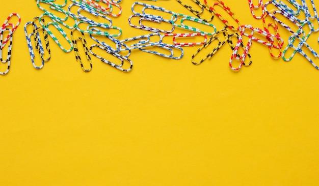 Lotto di graffette colorate su sfondo giallo. concetto di ufficio minimalista.