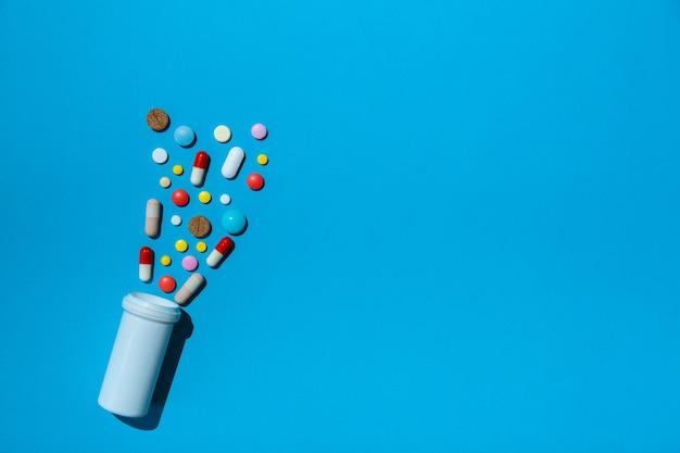 Molte pillole colorate su sfondo blu come concetto di trattamento medico con prescrizione medica
