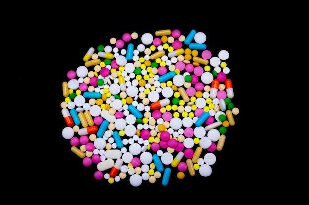 Molte pillole colorate su uno sfondo nero isolato
