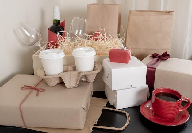 Un sacco di sacchetti e scatole di carta artigianale, bottiglia di vino e tazze di caffè sul tavolo, concetto di consegna.