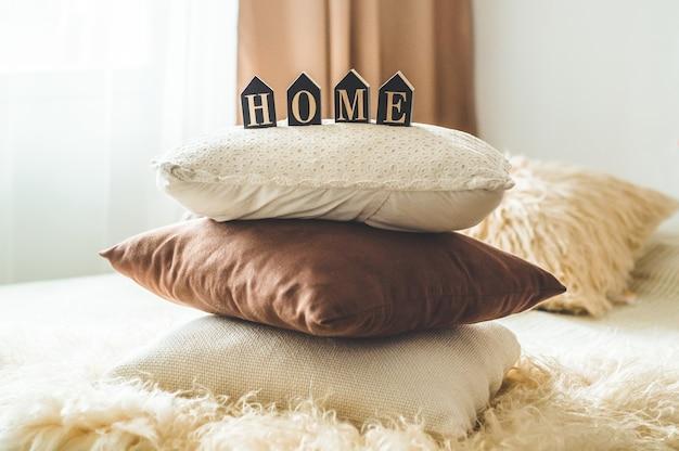Molti cuscini decorativi accoglienti e la scritta home. nell'interno della casa sul letto. primavera nell'interno della casa. concetto di casa