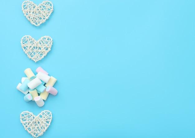 Un sacco di deliziosi marshmallow bianchi, gialli, blu e rosa con cuori di rattan bianco. stile piatto.