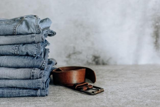 Lotto di diversi blue jeans blue jeans, pila di jeans e cintura marrone.