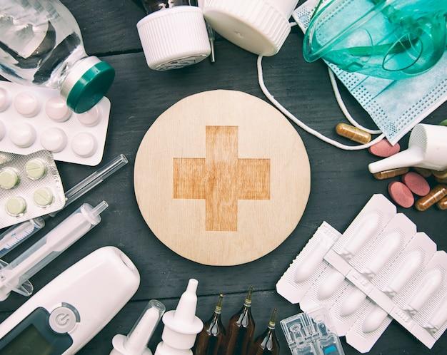 Molte droghe, pillole e altra medicina differenti sulla tavola nera di legno