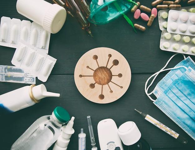 Un sacco di diversi farmaci, pillole e altre medicine sul tavolo bianco di legno e simboli di virus tra di loro
