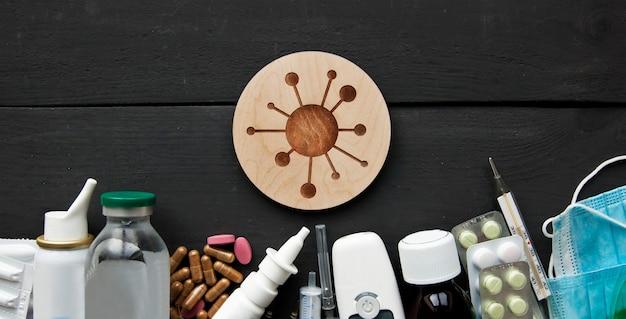 Un sacco di diversi farmaci, pillole e altre medicine sul tavolo bianco di legno