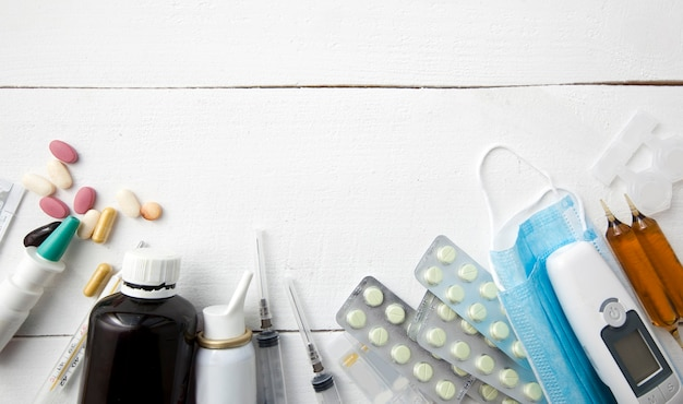 Un sacco di diversi farmaci, pillole e altri medicinali sul tavolo in legno bianco