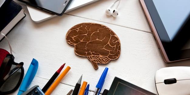 Un sacco di materiale didattico diverso sul tavolo di legno e un piccolo cervello di legno tra di loro