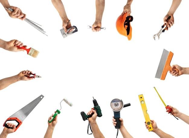 Un sacco di strumenti diversi nelle mani dell'uomo isolato su sfondo bianco
