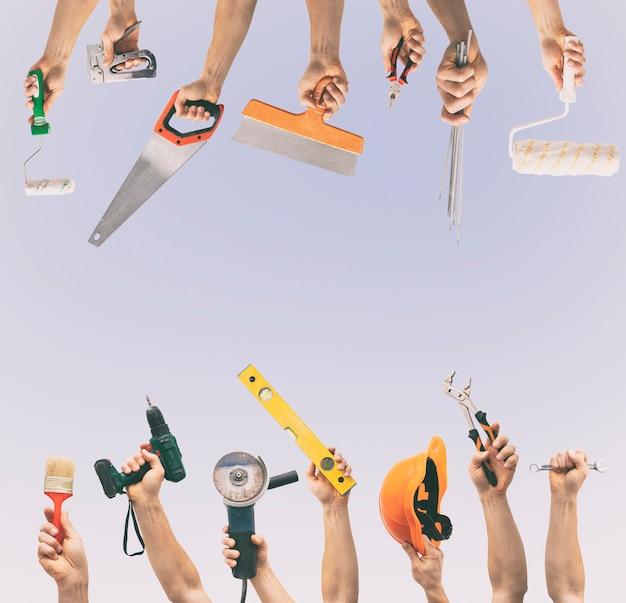 Molti strumenti diversi nelle mani dell'uomo isolati sullo sfondo bianco