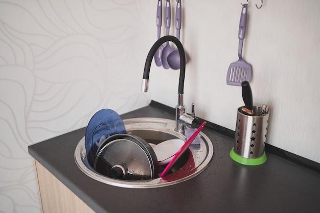 Un sacco di piatti sporchi nella cucina del lavandino in un appartamento in affitto è pigro pulire i piatti ogni giorno...