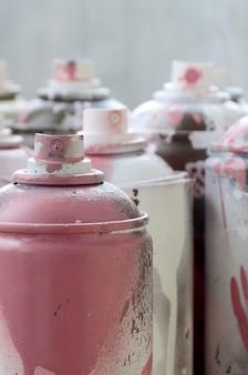 Un sacco di bombolette aerosol sporche e usate di vernice rosa brillante.