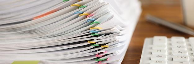 Molti documenti fissati con graffette multicolori che si trovano sul primo piano del tavolo