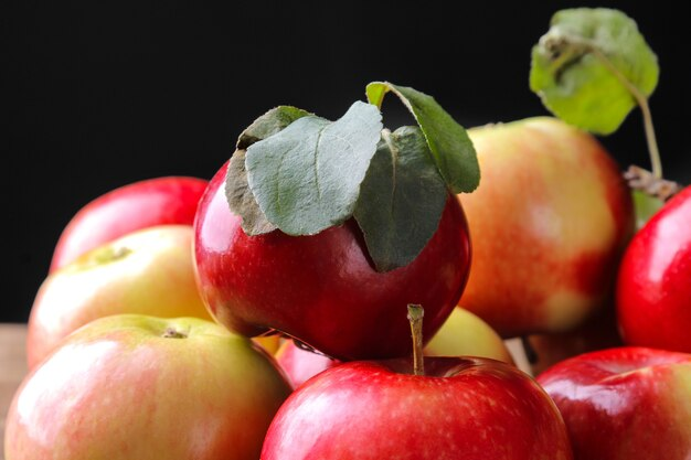 Molte belle mele rosse fresche con foglie verdi su sfondo nero